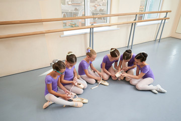 Six little ballet girls on the floor. Group of young pretty ballerinas in similar leotards preparing for the dance lessons.
