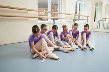 Group of young ballerinas at ballet class. Beatiful ballet dancers sitting on the floor and putting on ballet shoes. How ballerinas prepare for the lessons.