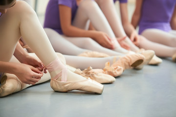 Ballet dancer tying slippers around her ankle. Young ballerina girl tying her ballet shoes sitting on the floor in ballet studio close up.