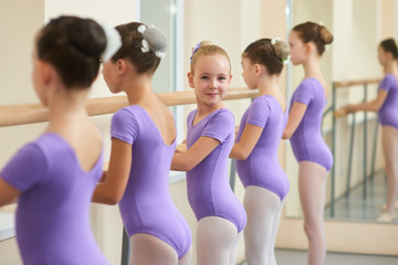 Young happy ballerina near ballet barre. Cute little ballet dancers practicing some dance element at a barre in a dance class. Professional school of ballet dance for kids.