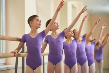 Group of ballerinas training at studio. Beautiful caucasian ballet girls practicing ballet at school. Hobby and skill.
