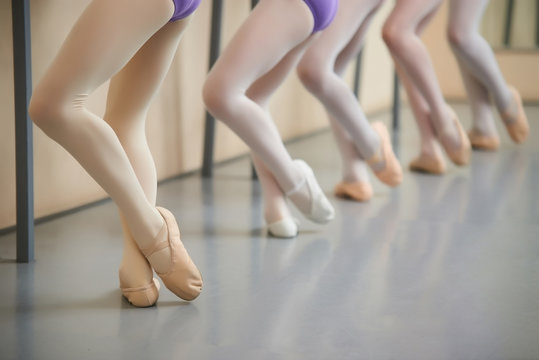 Ballerina training at hall, cropped image. Legs of young ballerinas having practice near ballet barre. Little dancers legs in pointe shoes doing exercises.
