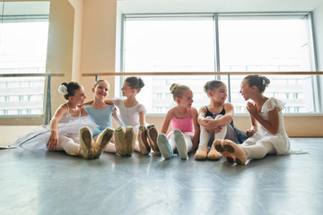 Young ballerinas sitting on floor and embracing. Cute little girls sitting on floor and laughing in ballet class together. They are best friends.