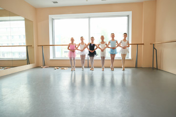 Young ballerinas in ballet position, copy space. Six young ballerinas in dresses and pointe shoes holding hands and standing in ballet studio.