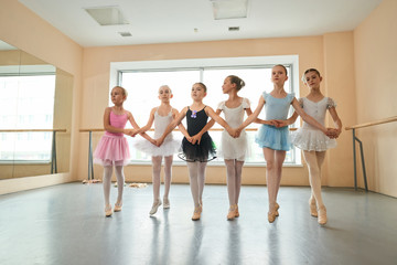 Group of ballerinas rehearsing before performance. Six young ballerinas in different dresses holding hands in ballet class. Choreography and ballet concept.
