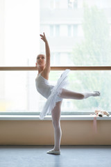 Young ballerina practicing dance move. Cute ballet girl in white tutu standing in ballet pose in dance class. Beautiful tender ballerina.