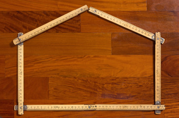 House Shaped Folded Measuring Stick on Wooden Background