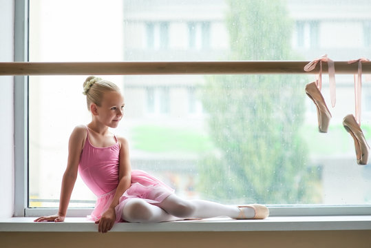 Beautiful ballet girl in pink leotard. Cute young ballerina sitting on window-sill and looking at pointe shoes on ballet barre. School of ballet dance.