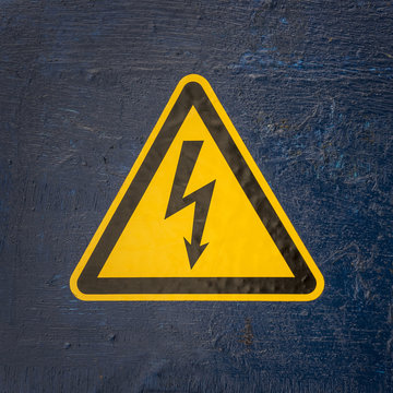 Yellow sign of high electrical voltage on the background of an old, shabby blue paint.