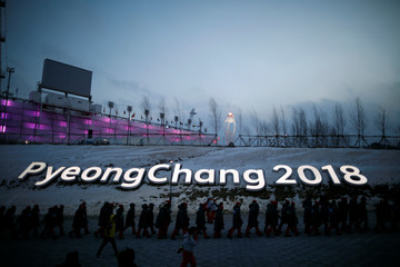 Volunteers walk as the Olympic cauldron is seen in the background at the Pyeongchang Olympic Stadium in Pyeongchang
