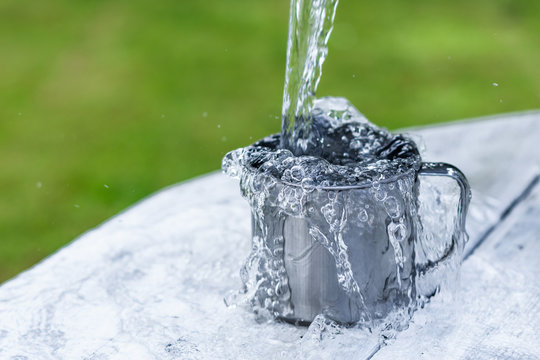 A steel mug with water and sprays on a white wooden table on nature background, life concept Water is pouring  out of the bucket into the mug on a white wooden table on nature background