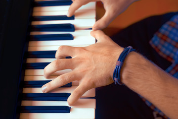 Man Playing Piano on Dramatic Dark Stage Close up