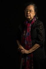Asian senior woman holding walking stick
