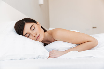 Portrait of a beautiful young woman sleeping in bed