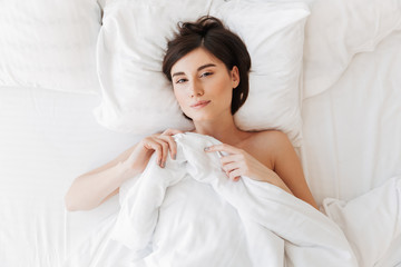 Top view portrait of a sleepy young woman lying in bed