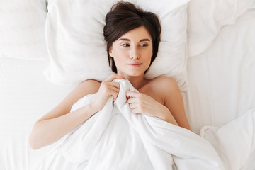 Top view portrait of an attractive young woman lying in bed