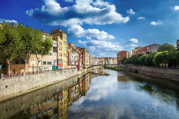 Colorful yellow and orange houses and bridge Pont de Sant Agusti reflected in water river Onyar, in Girona, Catalonia, Spain