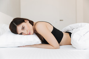 Portrait of a sensual young woman lying on a pillow