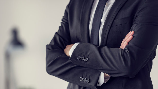 Torso of a businessman standing with folded arms