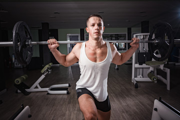 Barbell exercise, strong sexy man doing workouts to maintain his body strength