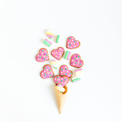 Gingerbread cookies and marshmallow in waffle cone on white background. Flat lay. top view.
