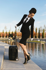 attractive young woman stewardess in uniform with a suitcase walking in the park