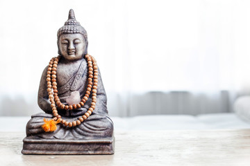 Buddha statue with beads in bright white treatment room.
