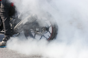 sport motorbike wheel drifting and smoking on track, background for display a text or product.
