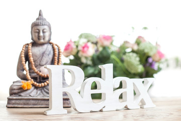 Buddha statue with beads. Buddha statue and the word relax in wood lettering.