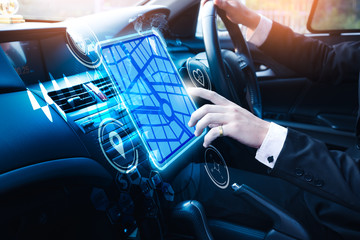 The abstract image of businessman point to the navigation hologram in car cockpit. the concept of communication, network, insurance, financial and internet of things.