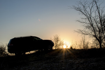 silhouette of an SUV standing on a hill, at sunset