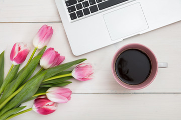 Women's day. Pink tulips, laptop and a cup of coffee on an white desk, top view