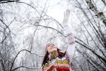 Photo of smiling brunette looking up in knitted hat and scarf catching snowflakes in winter forest during day