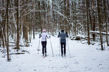 Image from back of sports woman and man skiing in winter forest