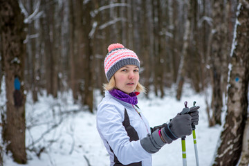 Photo of smiling woman with skis in winter forest