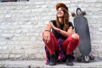 Cute trendy urban girl with longboard outdoors