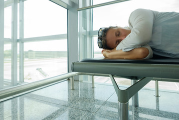 Delayed aeroplane concept. Tired passenger is sleeping in airport terminal and waiting for airplane arrival.