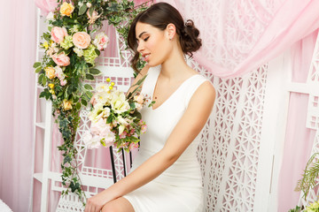 Image of beautiful woman in white dress on background of flowers