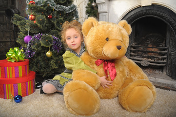 little girl with a big bear by the fireplace