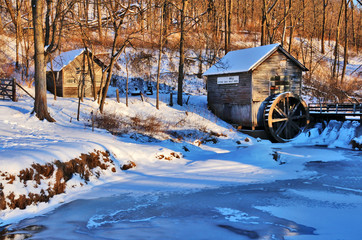 Rural landscape with old abandoned watermill in woods. Beautiful winter view with frozen river in front of old wooden water mill and barn in a snowy forest during sunset.