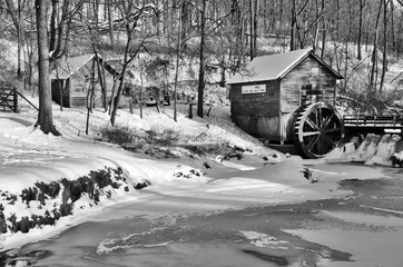 Rural landscape with old abandoned watermill in woods. Beautiful winter view with frozen river in front of old wooden water mill and barn in a snowy forest during sunset. Black and white composition.