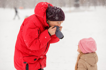 Photo of father dressing his daughter mitten in winter park