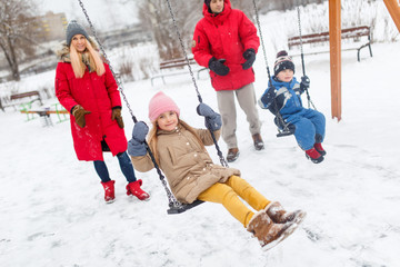 Photo of girl and boy swinging in winter in park with parents
