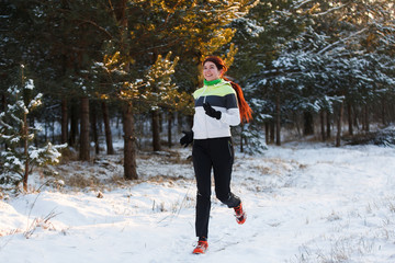 Photo of athlete brunette in sneakers on morning run against tree in winter
