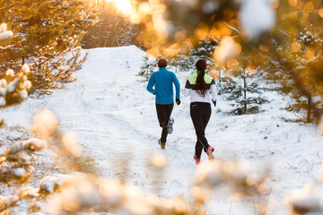Image from back of running two athletes in winter park