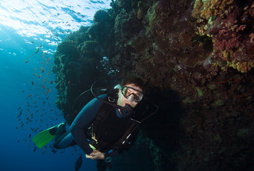 Scuba diver exploreds coral reef