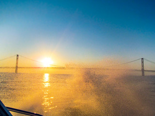 Mackinac Bridge and bright sun rays are visible through water splashes. View from the lake surface when the boat moves at high speed and creates a waves and water sprays at sunset in Michigan, USA.