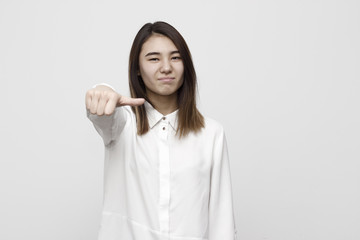Woman giving an equal thumb gesture with a grimace showing that she is undecided, abstaining, impartial or indifferent in a vote, upper body
