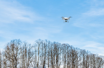 White Drone flying in a cloudy blue sky.
