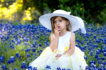 Fototapete - Adorable little girl in a yellow dress and white easter bonnet in a field of bluebonnets